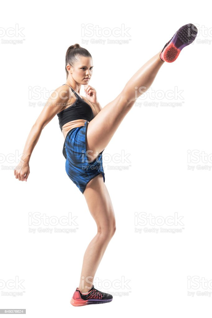 Stopped action motion of tough woman kickboxing fighter doing high kick. stock photo