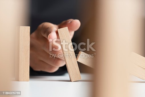 Finger is stopping chain reaction of dominos who are about to fall in front of a dark background.