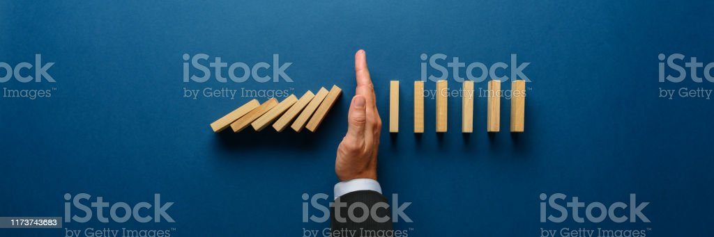 Stopping collapsing dominos Wide view image of businessman hand stopping collapsing dominos in a conceptual image. Top view over navy blue background. Achievement Stock Photo