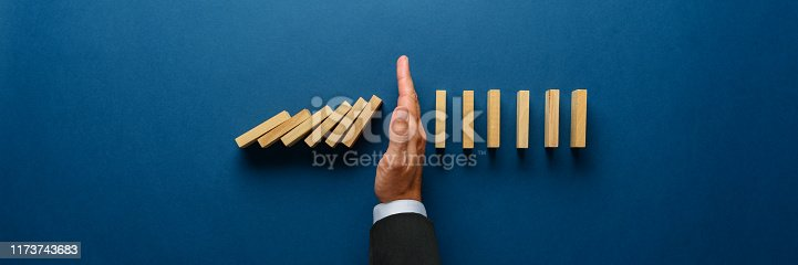 istock Stopping collapsing dominos 1173743683