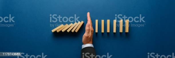 Stopping Collapsing Dominos Stock Photo - Download Image Now