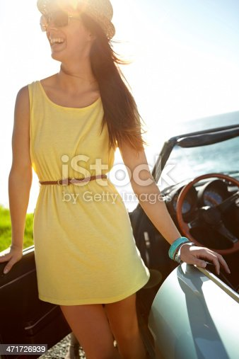 A beautiful young woman standing next to her convertible by the side of the ocean