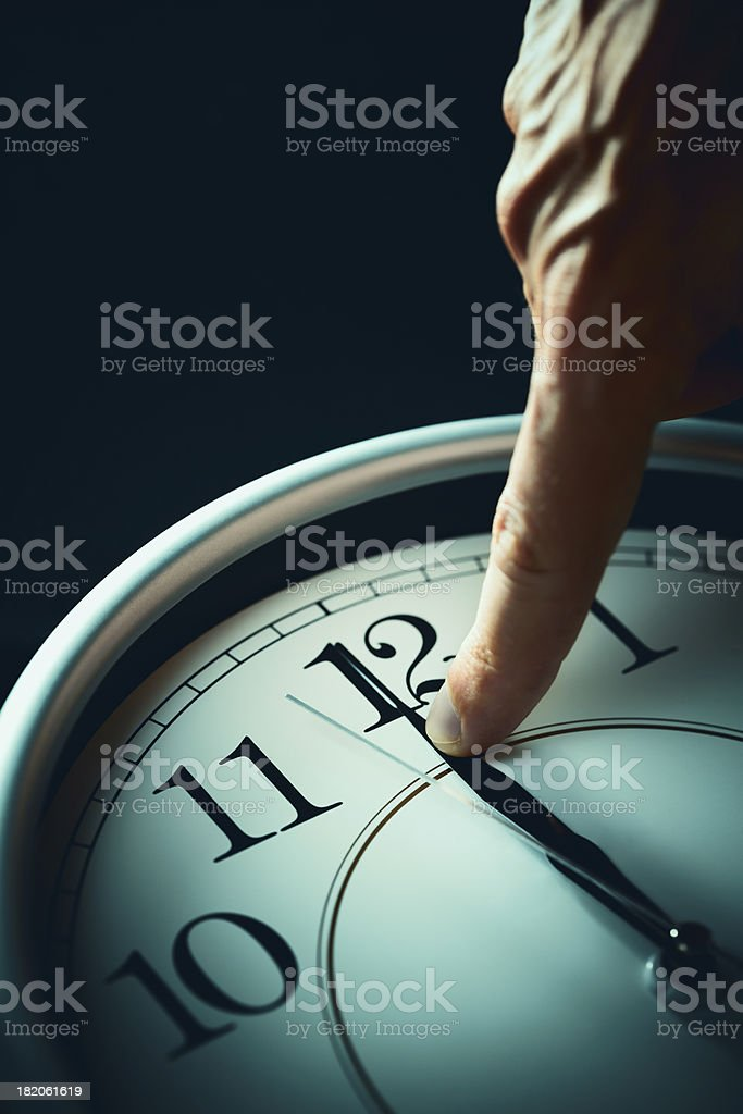 \'Close-up of an index finger stopping a clock\'s hands on twelve...