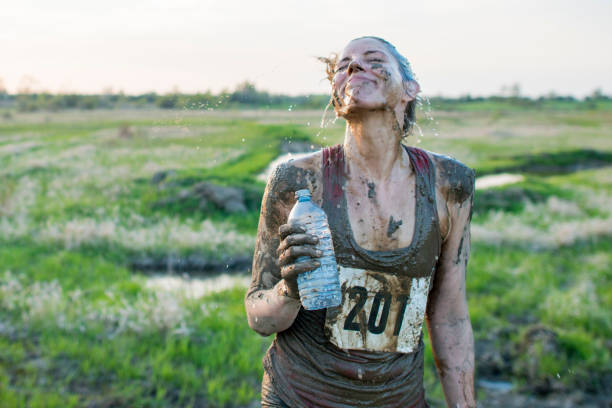 Stopping To Drink A Caucasian woman is outdoors, participating in a mud run. She is wearing athletic clothing and shoes.  She is covered in mud and water is dripping from her face. She is holding a water bottle and laughing. mud run stock pictures, royalty-free photos & images