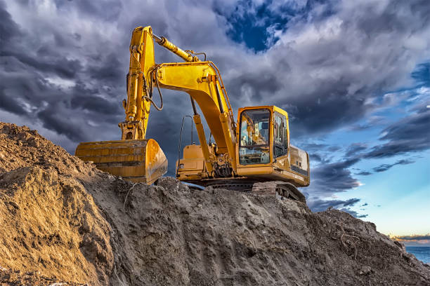 A stopping yellow excavator A stopping yellow excavator at an incredibly beautiful sunset construction machinery stock pictures, royalty-free photos & images