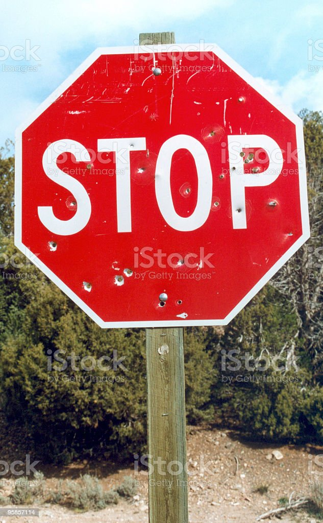 Stopsign with holes from a shotgun royalty-free stock photo