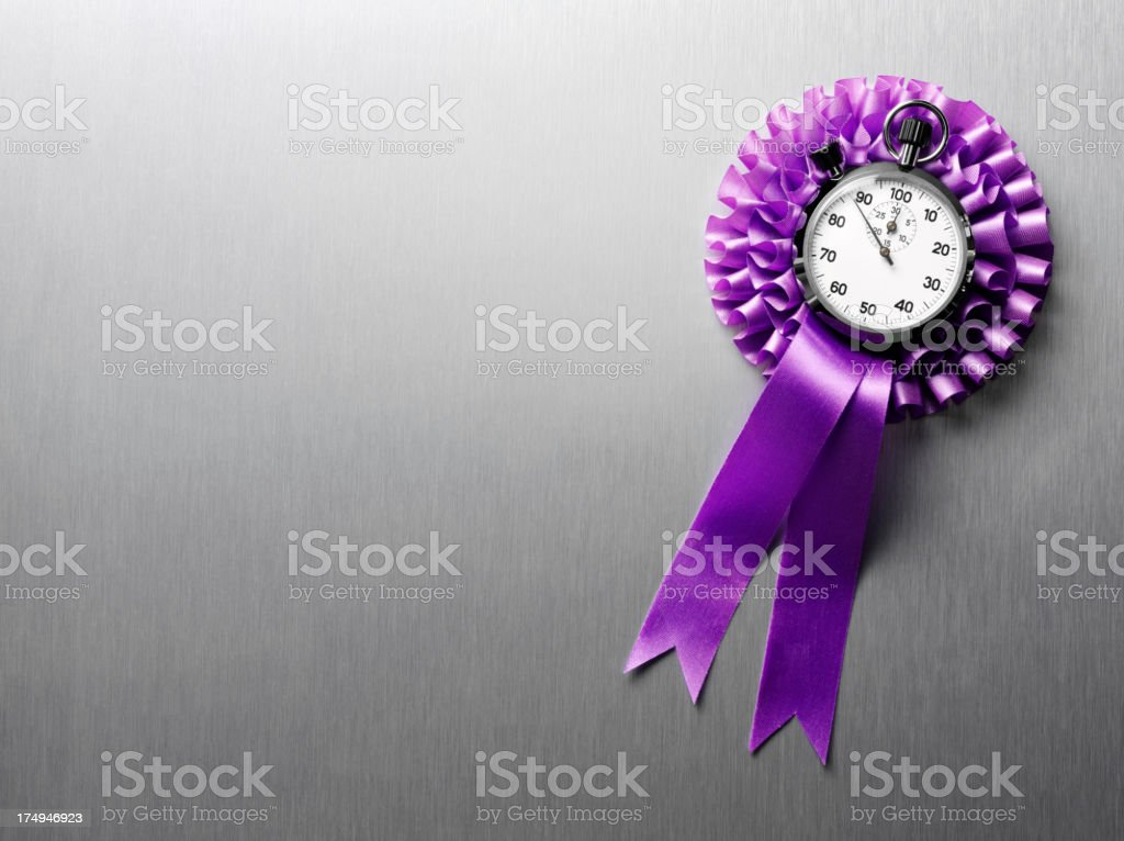 Stopwatch and a Purple Ribbon Rosette with Copy Space royalty-free stock photo