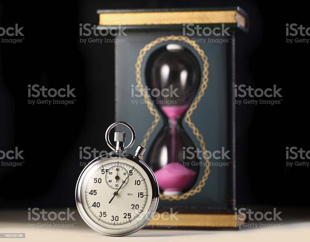 Stopwatch and sand watch on black background stock photo
