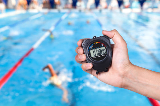 stopwatch holding on hand with competitions of swimming background. - watch timepiece stock photos and pictures