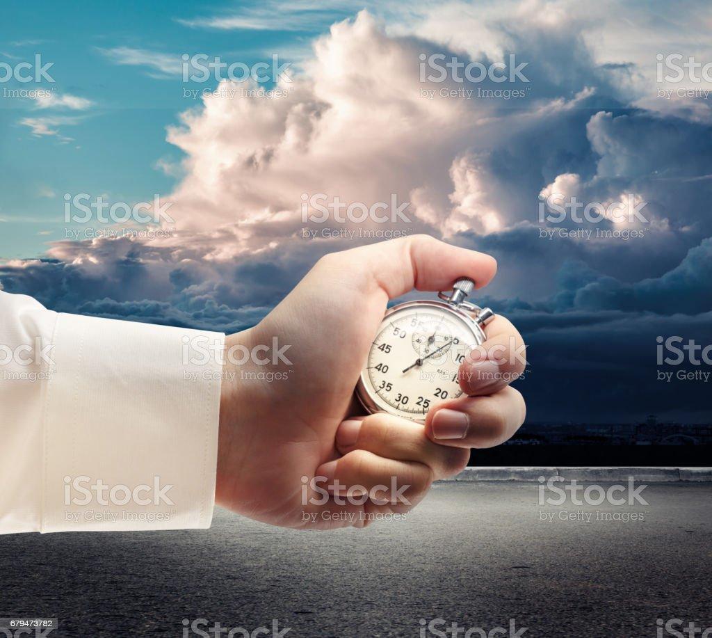 Stopwatch in male hand on dark sky 免版稅 stock photo