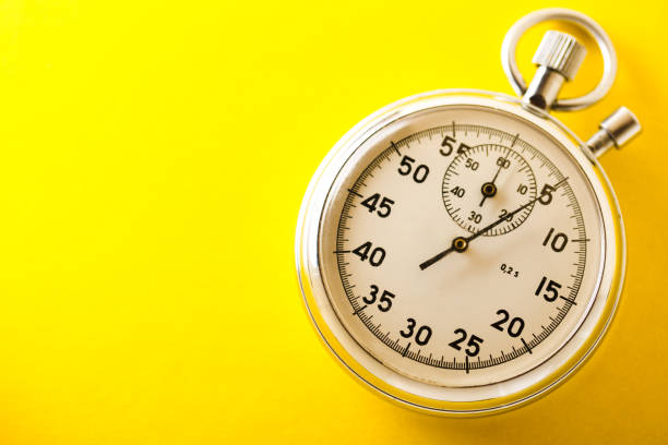 stopwatch on yellow background - stopwatch stockfoto's en -beelden