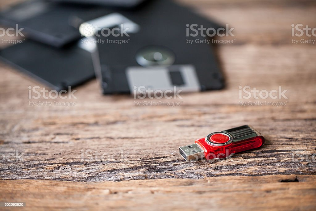 USB storage drive and floppy disks on a wooden table stock photo