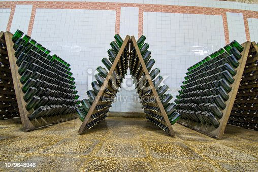 Storage hall of white sparkling wine bottles in the cellars of winery, sparkling wine fermenting on stands