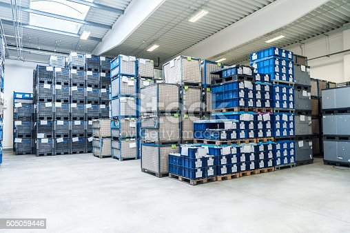 Horizontal image of modern new warehouse of large factory. The warehouse is filled with boxes on pallets. Logistics, freight, shipping, receiving. No people, space for copy.