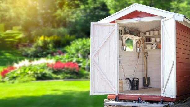 Storage shed filled with gardening tools. Storage shed filled with gardening tools. Beautiful green botanical garden in the background. Copy space for text and product display. shed stock pictures, royalty-free photos & images