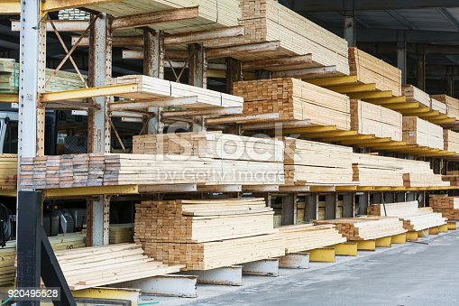 Warehouse at a lumberyard with stacks of construction material on shelves.