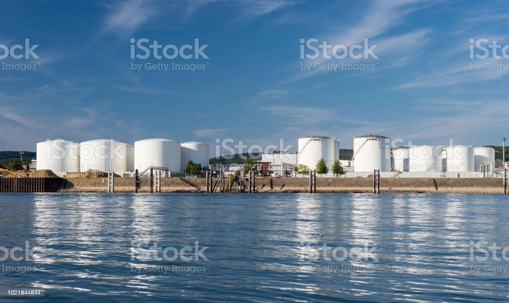 Lagersilos, Tanklager von Erdöl und Benzin an den Ufern des Flusses in den alten Bundesländern auf einen wunderschönen blauen Himmel mit Wolken. – Foto