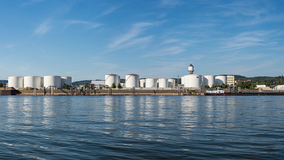 Storage silos,fuel depot of petroleum and gasoline on the banks of the river in western Germany on a beautiful blue sky with clouds. High resolution panorama, visible tanker barge.