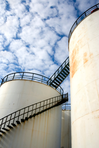 close up shot of oil storage tanks over cloudy sky.