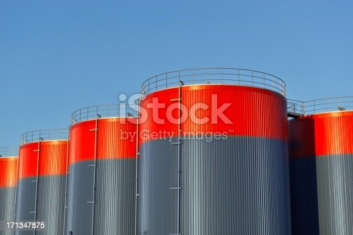 Three storage tanks with a blue sky with copy space in the background.