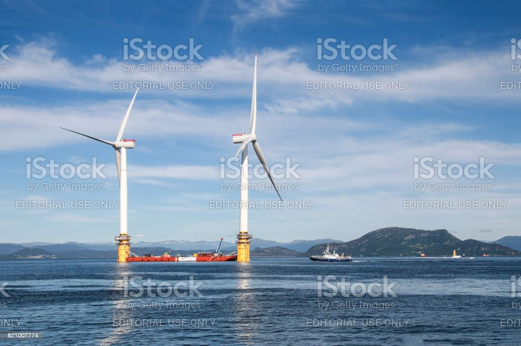 Stord, Norway-June 27, 2017: two of five floating wind turbines being prepared to sail off to the world's first floating wind farm stock photo