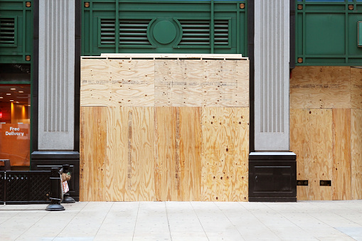 Store closed during the COVID-19 pandemic, with boarded up windows to protect against looting