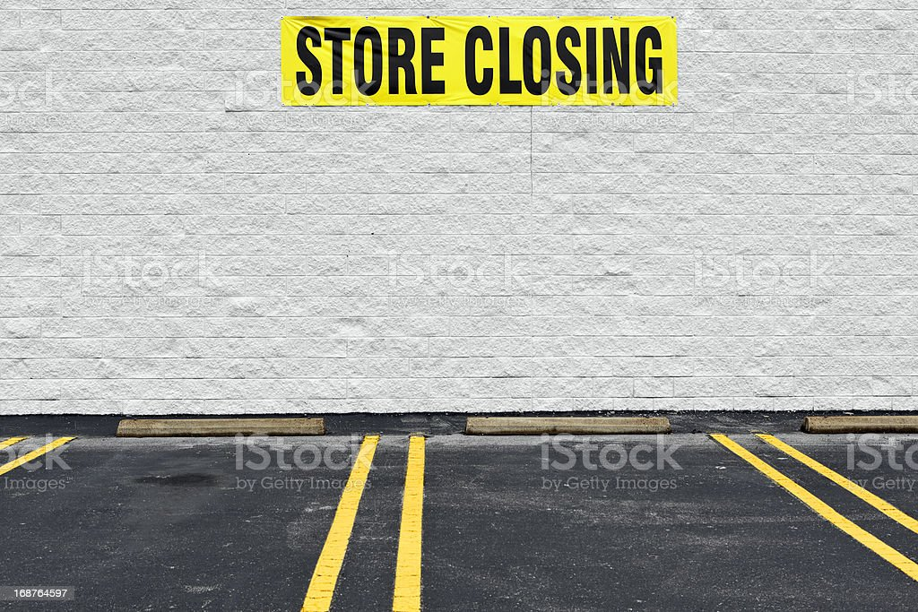 Store Closing Banner over Empty Parking Spaces stock photo