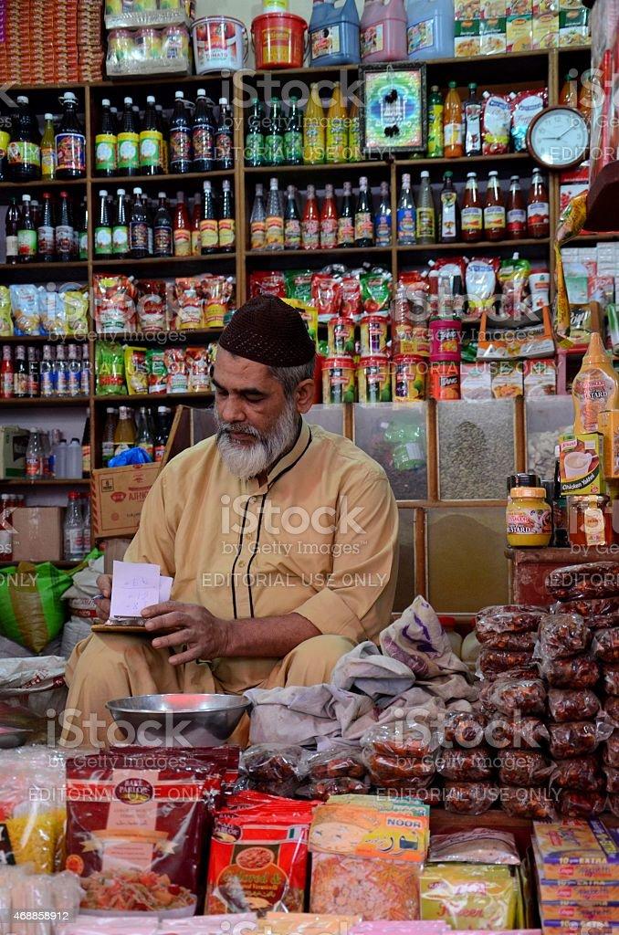 Store keeper tends paperwork Empress Market Karachi Pakistan stock photo