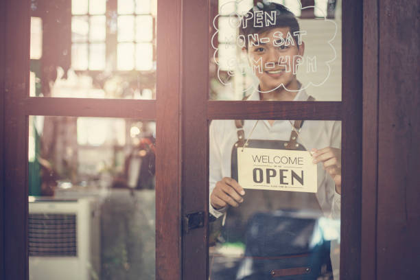 Store owner turning open sign broad through the door glass and ready to service. stock photo