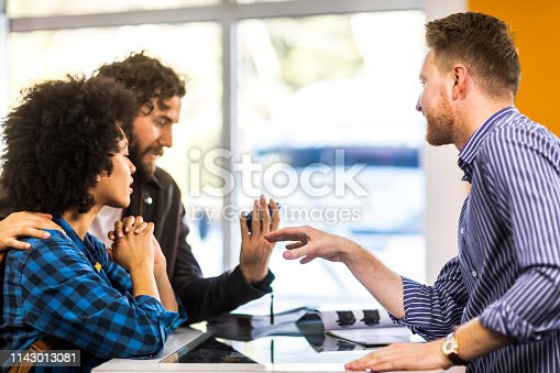 Salesman explaining the functionality of a small blue compact camera to a young male shopper in a camera store.