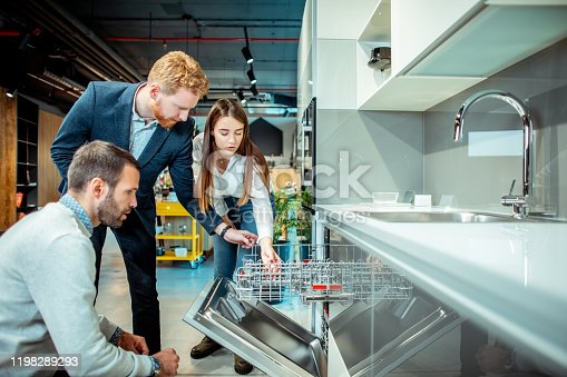 Shop salesman explaining the features of a new dishwasher model to a young shopping couple in a kitchen appliances store.