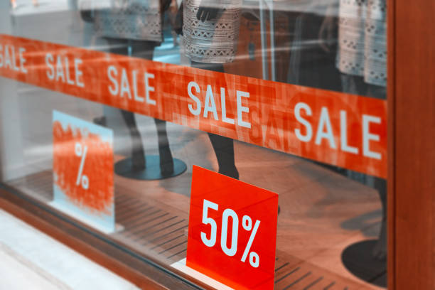 store window at sales store window at sale with 50%.red banner on the window. discount store stock pictures, royalty-free photos & images