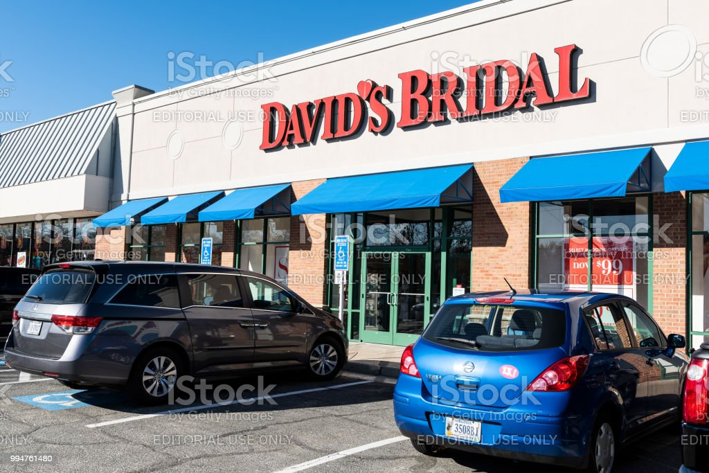 Storefront of David's Bridal retail store, shop selling wedding dresses, clothes, garment with sign, parked cars, parking lot stock photo