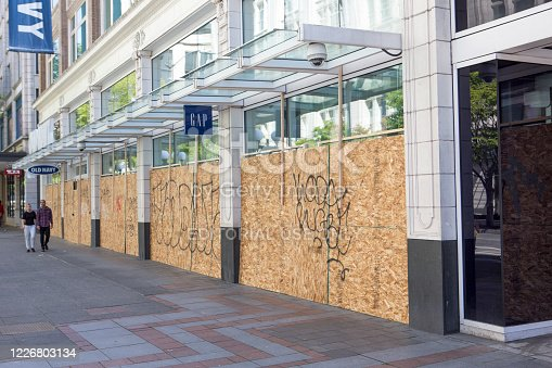 The city of Seattle is one of the epicenters of the coronavirus COVID-19 outbreak.  The government shutdown of non-essential businesses has closed many public places including shops, restaurants, bank lobbies and more.  The Gap and Old Navy stores in downtown is closed during the crisis.  Two people in the distance walk by the boarded up store fronts.
