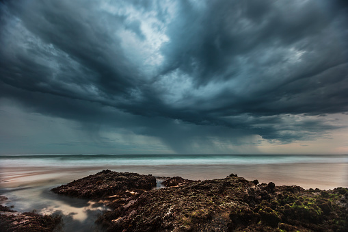 Storm cell moving out to sea over a coastal beach environment