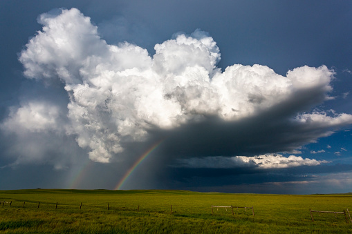 Storm cloud with silver lining and double rainbow over green field in Montana