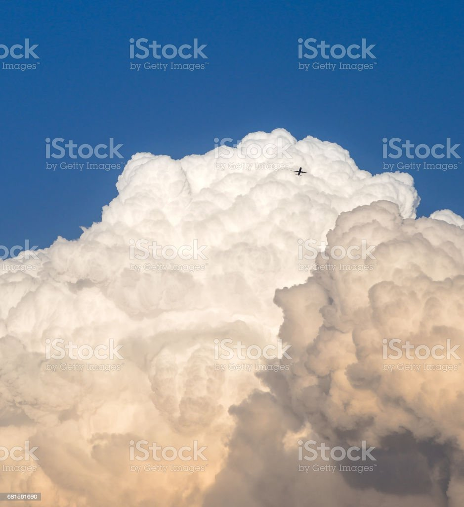 Storm clouds and a distant airplane stock photo