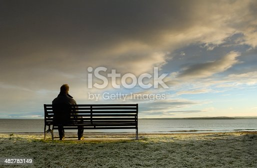 Man sitting on bench looking out at storm clouds approaching.
