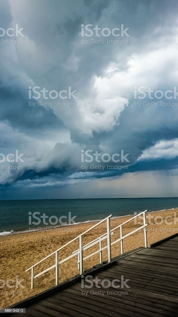 Storm clouds at beach with railing stock photo