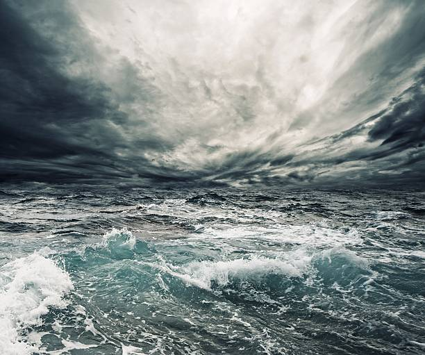 storm clouds over a churning ocean - storm stock photos and pictures