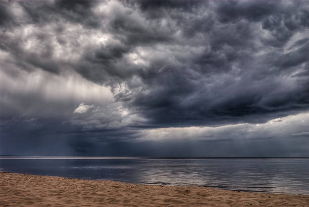 storm clouds over the sea - regen zon stockfoto's en -beelden