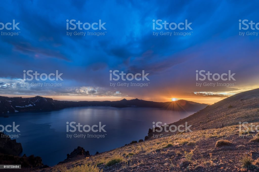 Storm Clouds Push in at Sunset Over Crater Lake stock photo