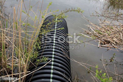 Excess water runoff culvert pipe from a golf course into a holding pond.
