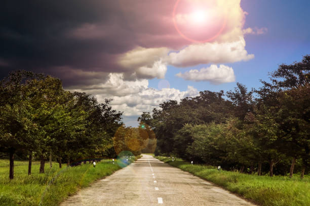 A Storm Front is Coming Country Road in Front of an Approaching Storm approaching stock pictures, royalty-free photos & images