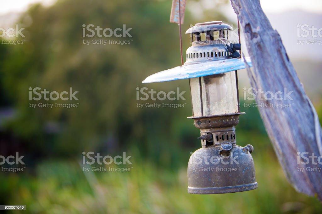 Storm lantern hanging on the old wood pole. stock photo