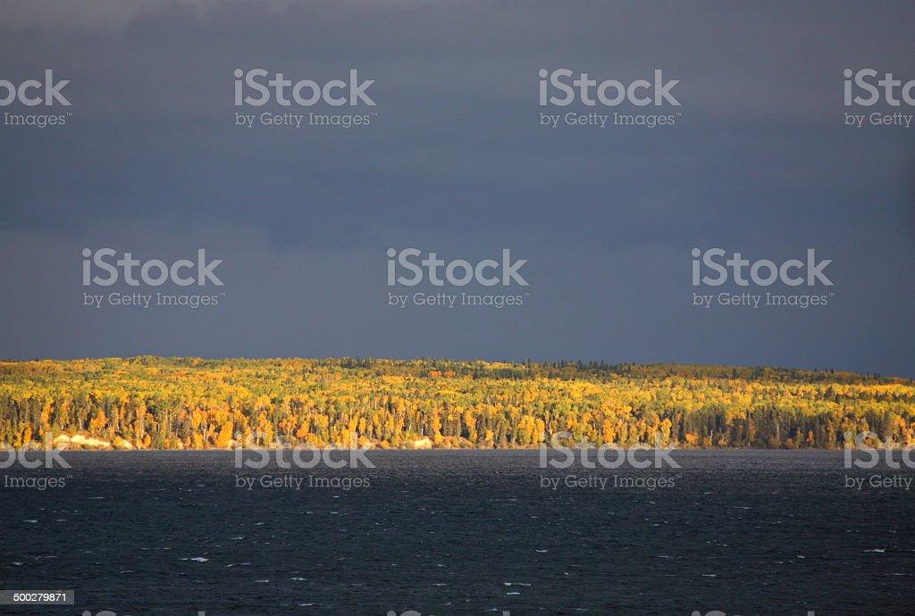 Storm over fall trees at Waskesiu Lake in Saskatchewan stock photo