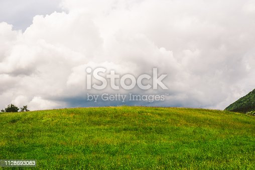 Stormy clouds over the green hill