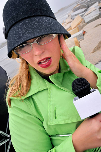 Storm Reporter Woman Holding Earpiece stock photo