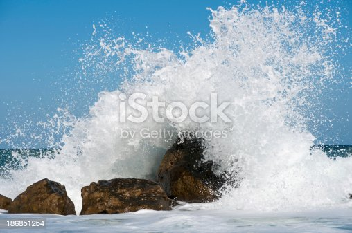 A huge wave crashes on to the rocks.