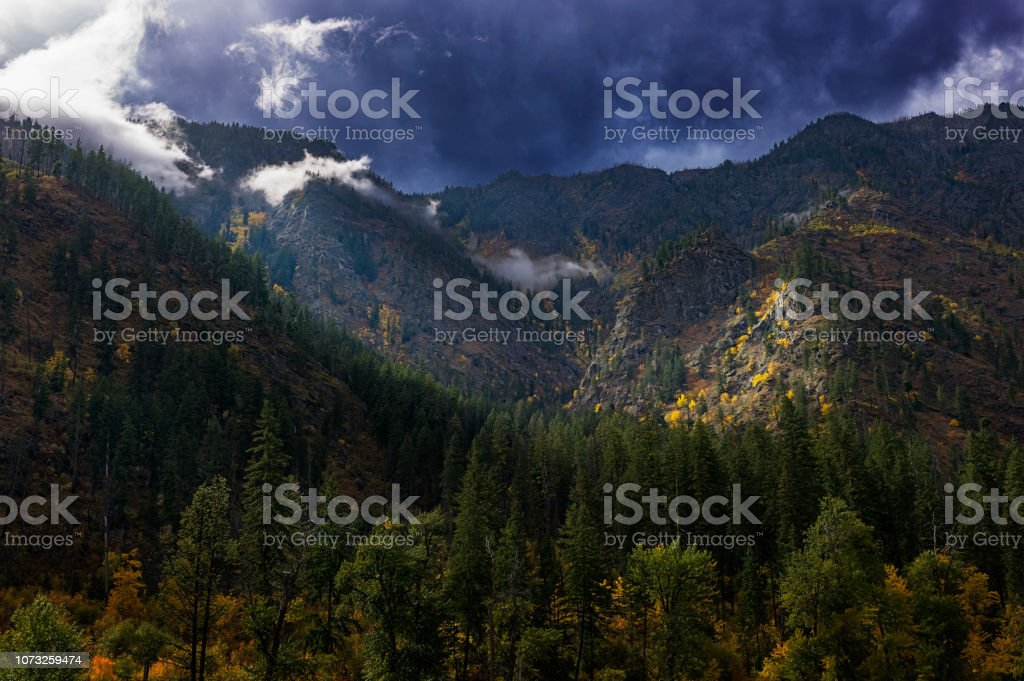 Stormy autumn sky with the sun breaking through over the mountains in North Central Washington stock photo